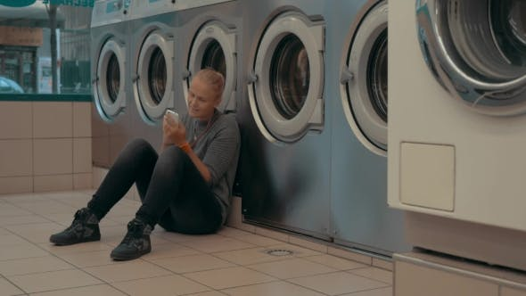 Thumbnail for Woman With Mobile Waiting For The Laundry