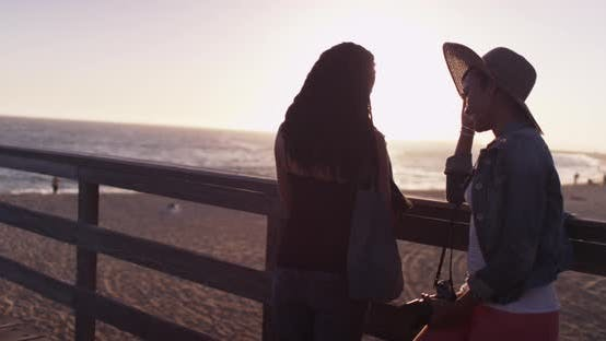 Thumbnail for Two black women best friends leaning against pier at sunset