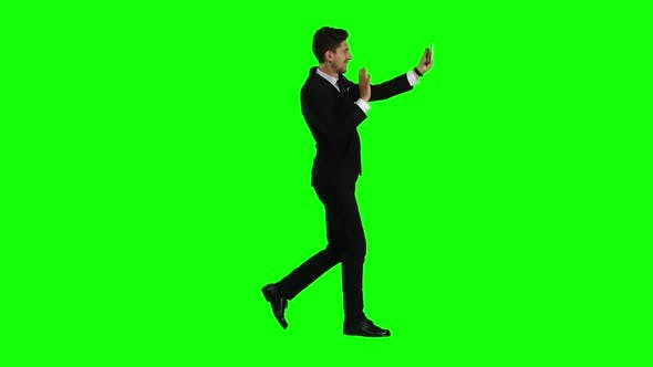 Thumbnail for Businessman Walks, Thumbs a Notebook, and Makes a Selfie. Green Screen. Side View