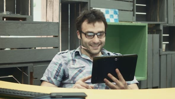 Cover Image for Man Talking Over Tablet At Workplace