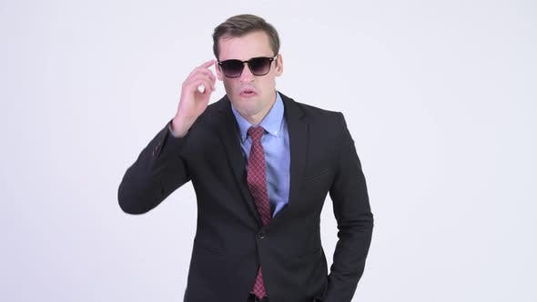 Thumbnail for Young Handsome Businessman Removing Sunglasses and Looking Shocked