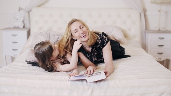 Thumbnail for Woman Reading Book To Her Daughter And Kisses Her