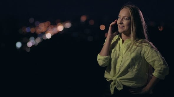 Thumbnail for Happy Woman Talking On Mobile Phone At Night