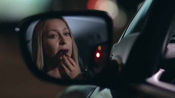 Thumbnail for Young Woman Applying Red Lipstick in the Car