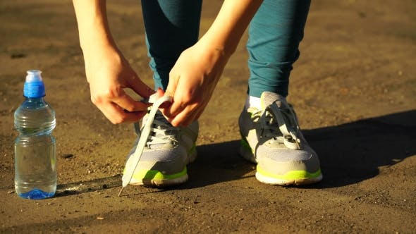 Thumbnail for Girl Stopped Running To Tie The Laces On Running Shoes. Fitness Girl Training Outdoors.