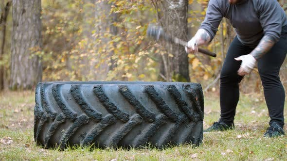 Cover Image for A Big Man Bodybuilder Hitting the Truck Tire with a Hammer - Autumn Forest