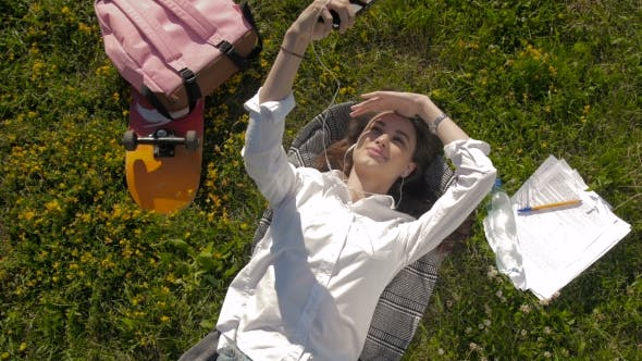 Thumbnail for Beautiful Young Woman Laying On The Grass And Listening To Music. Making Selfie.