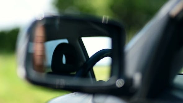 Thumbnail for Young Woman Driver Looking At Car Side View Mirror