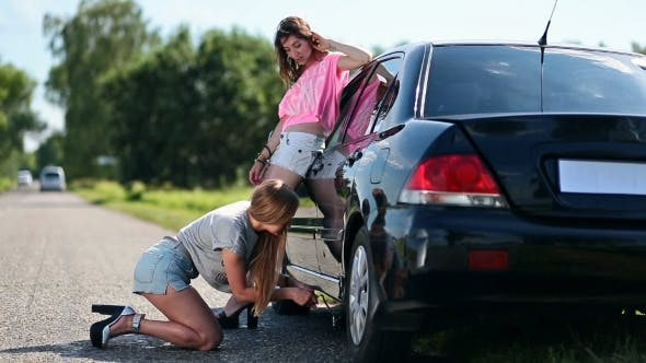 Thumbnail for Cute Woman Jacking Up Her Car to Change Flat Tire