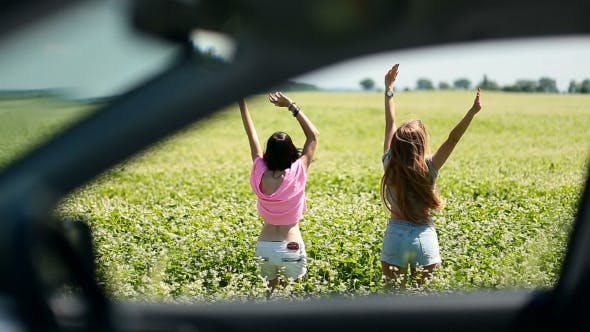 Thumbnail for View Through Car Window Of Women Jumping In Field