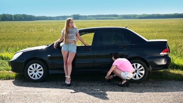 Cover Image for Cute Girl Lifting Up Car Using Screw Jack On Road