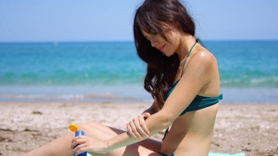 Thumbnail for Young Woman Applying Sun Cream To Her Legs