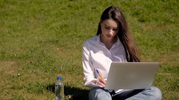 Thumbnail for Cute Student Girl Working With Laptop And Papers In Park Of An University Campus