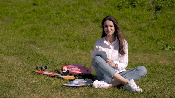 Thumbnail for Beautiful Happy Smiling Brunette Using Tablet PC Sitting In Park On a Sunny Day