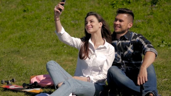Thumbnail for Young Couple Make Selfi Sitting On Grass In a Park