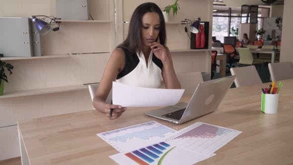 Thumbnail for Indian Business Woman Working With Financial Documents In The Modern Office.