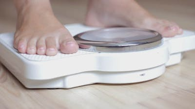 The Girl Checks for the Weight on the Scales