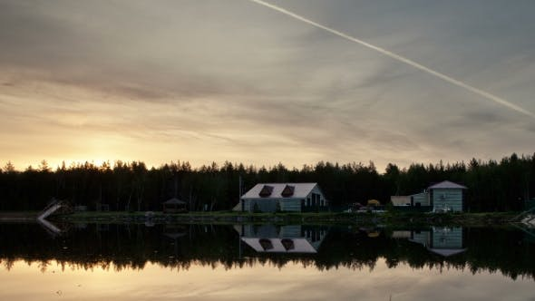 Thumbnail for Houses On The Edge Of The Forest. Pond. Sunset. Trace Of Aircraft In The Sky.