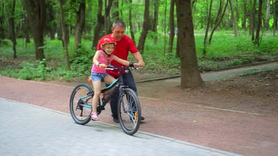 Father teaching daughter to ride bike at urban park. Child girl learning biking with the dad's help.