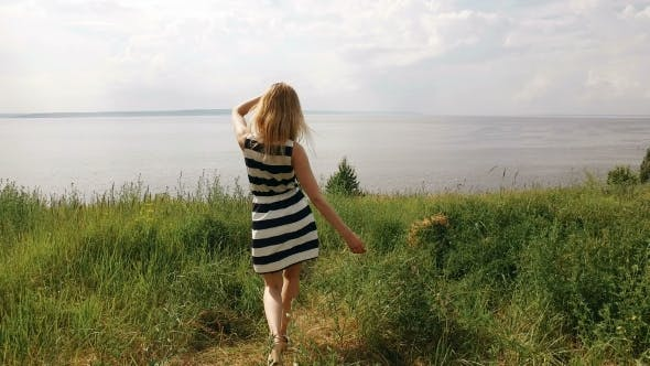 Thumbnail for Young Shapely Blonde Is Walking On a Field, Looking On a Sea In Summertime