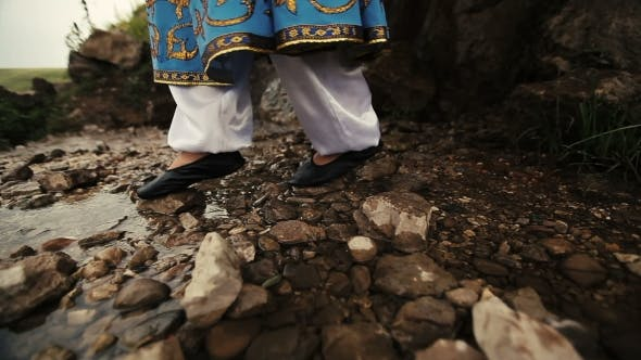 Thumbnail for Woman In National Blue Bright Caucasian Suit Walking Through Stream. Rocky Road