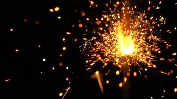 Thumbnail for Burning Bright Orange Sparkler Against Black Background