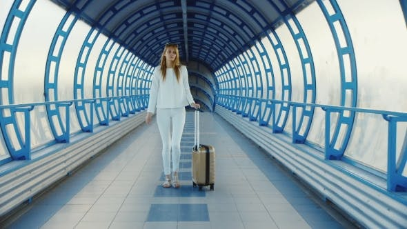 Thumbnail for Young Business Woman With Travel Bag On Wheels Is On The Transition From The Terminal At The Airport