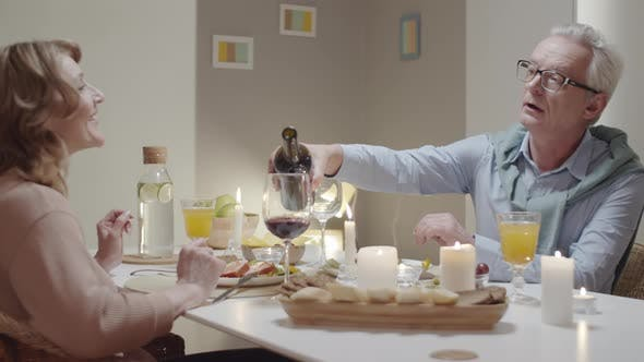 Thumbnail for Senior Man Filling Glasses with Wine and Talking with Wife at Dinner