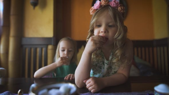 Thumbnail for Two Cute Little Girls Are Eating In a Cafe