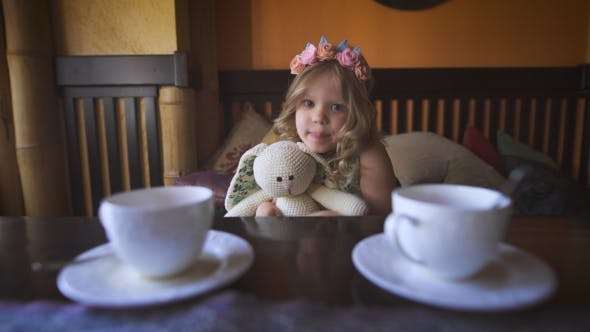 Thumbnail for A Little Pretty Girl Is Sitting On The Sofa At a Cafe And Hugging Her Stuffed Rabbit.