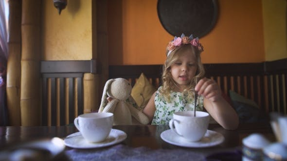 Thumbnail for A Little Girl Is Having Tea With Her Stuffed Rabbit In a Cozy Cafe.
