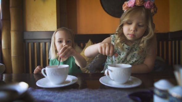 Thumbnail for Two Cute Little Girls Are Having Tea In a Cafe