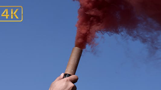 Smoke Bomb in Hand on Sky Background