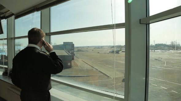 Thumbnail for Airport Security Officer In Uniform Watching Aerodrome Traffic And Talking On Phone.