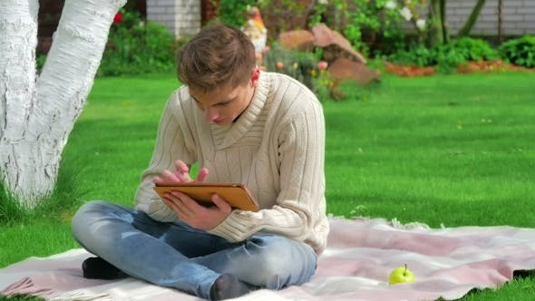 Cover Image for Guy Sitting In The Garden And Using Digital Tablet
