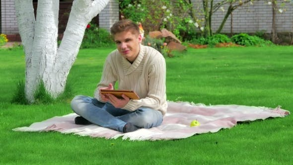 Thumbnail for Guy Sitting On The Lawn With Digital Tablet