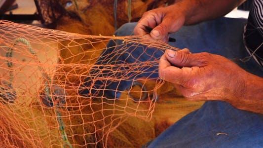 Thumbnail for Fisherman Repairs Fishnets 1