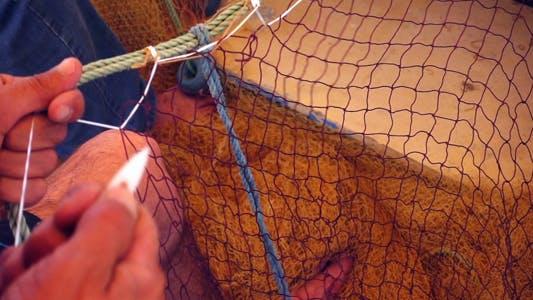 Thumbnail for Fisherman Repairs Fishnets 2