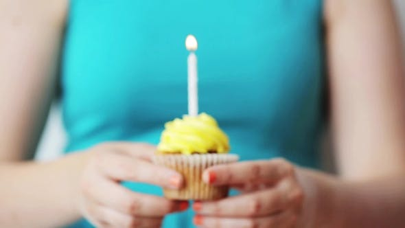 Thumbnail for Woman With Burning Candle On Birthday Cupcake