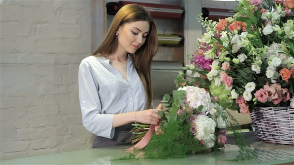 Thumbnail for Female Florist Demonstrate a Bouquet Of White Flowers At Flower Shop