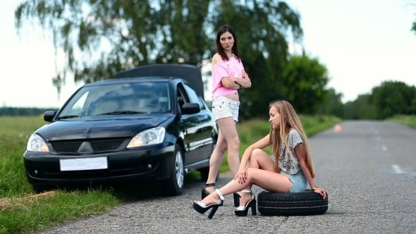 Cover Image for Annoyed Woman Sitting On Spare Wheel On The Road