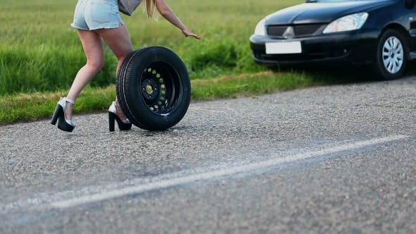 Thumbnail for Sexually Dressed Woman Rolling Spare Wheel On Road