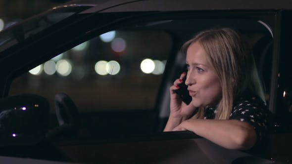 Thumbnail for Attractive Blonde Woman Talking On Phone In Car