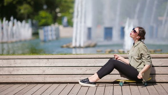 Young Beautiful Girl Listening Music And Enjoy Her Weekend On Wooden Bridge. Beautiful Hipster Woman
