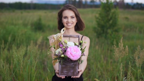 Thumbnail for Fresh Flowers In a Stylish Drawer. Beautiful Brunette In a Flowery Field In The Evening.