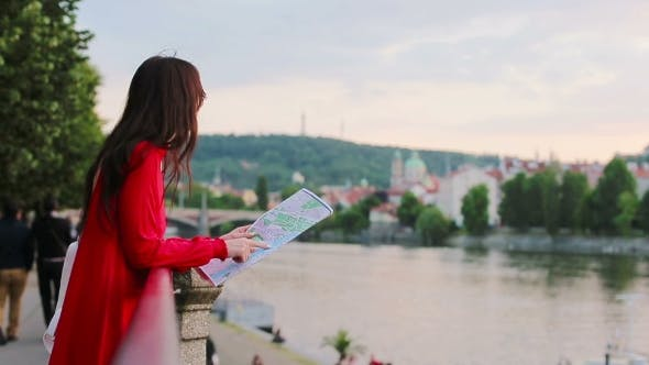 Thumbnail for Happy Young Woman With a City Map In Europe Background Famous Bridge. Travel Tourist Woman With Map
