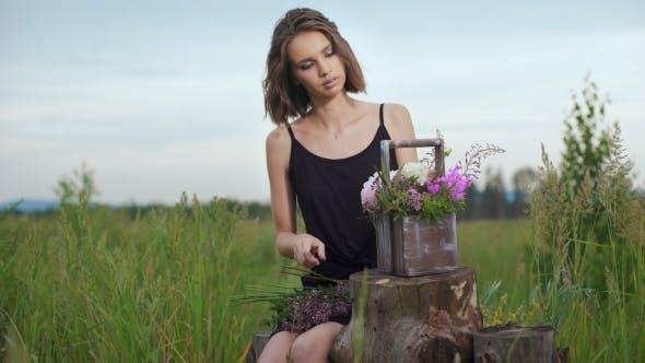 Thumbnail for Slim Girl In Black Dress Works Of Flowers At Sunset