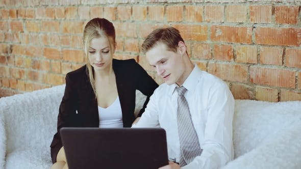Thumbnail for Businesswoman And Businessman Discussing Business With Laptop On The Sofa