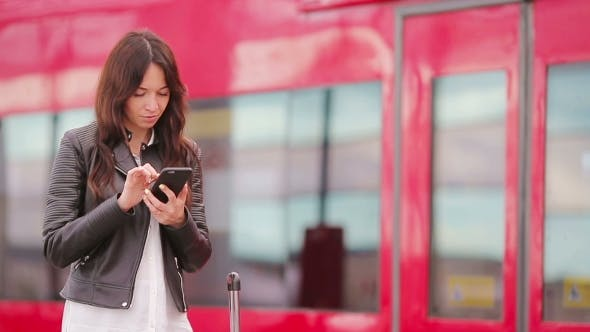 Thumbnail for Young Woman With Luggage Looking on Cellphone at a Train Station