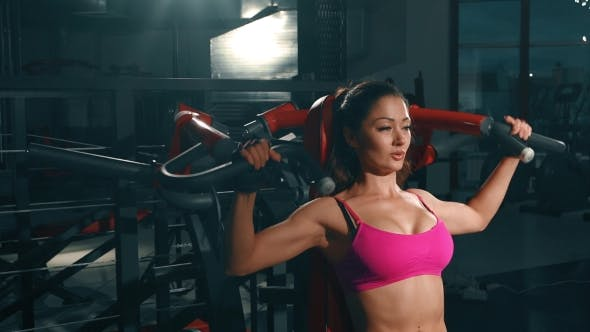 Thumbnail for Young Girl Flexing Muscles On Gym Machine